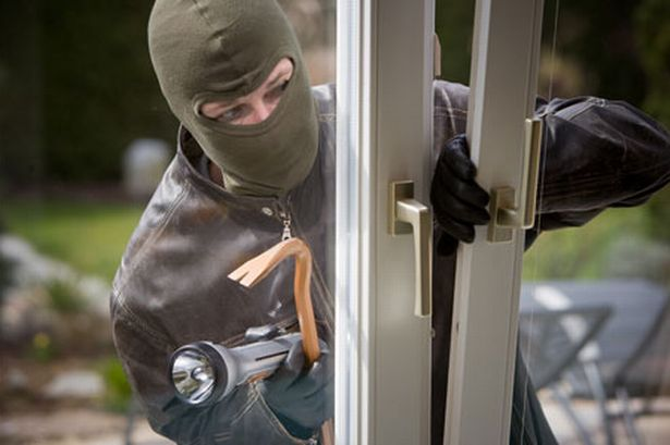 picture of masked burglar entering home